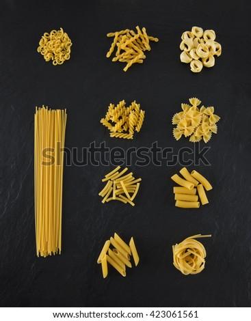 Selection of pasta on black slate background, Spaghetti, Penne, Tagliatelle, Fussili, Gemelli, Maccheroni, Rigatoni, Farfalle, Gobetti, Tortellini  - stock photo