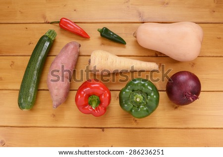 Selection of raw vegetables - courgette, bell peppers, chili, sweet potato, parsnip, butternut squash and red onion - on a wooden table - stock photo