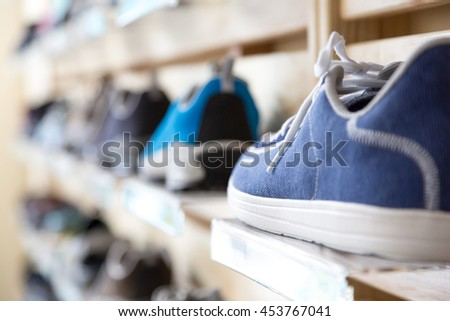 Selection of Summer Season sporty and travel Footwear on wooden Wall of Retail Shop