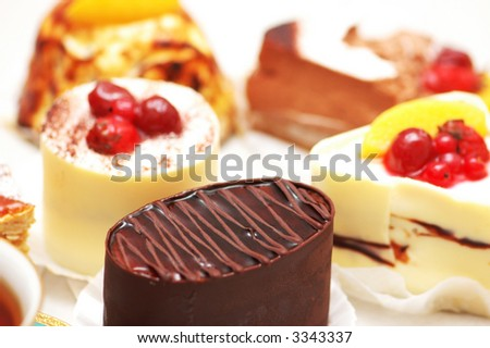 Selection of sweet cakes and tea on the table - stock photo