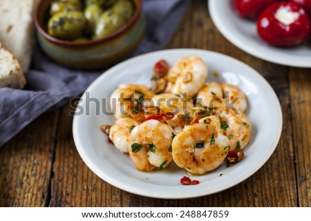 Selection of tapas dishes: prawns, squid, stuffed peppers - stock photo