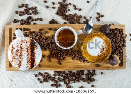Selection of types of coffees on a wooden board: frothy cappuccino with cocoa on top, espresso and latte. - stock photo