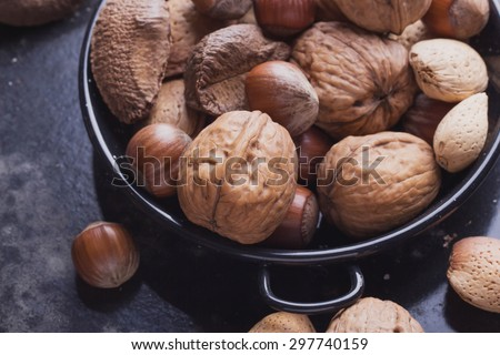 Selection of various nuts: almonds, Brazilian, walnuts in the tiny vintage spanish black metal plate, black background, top view - stock photo