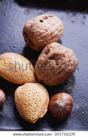 Selection of various nuts: almonds, Brazilian, walnuts on a vintage black metal tray - stock photo