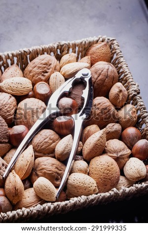Selection of various nuts: almonds, Brazilian, walnuts on a vintage square basket with a nut cracker - stock photo