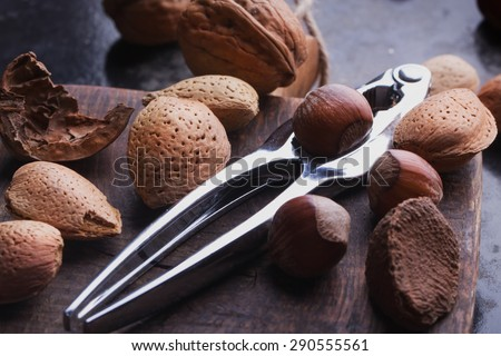 Selection of various nuts: almonds, Brazilian, walnuts on a vintage wooden board with a nut cracker - stock photo