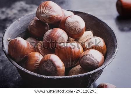 Selection of walnuts in the vintage copper chinese bowl, black background - stock photo