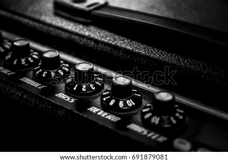 selective and blur focus.knob on head controller.black professional electric guitar amplifier.low key tone image.concept for live music festival.Instrument on stage,abstract musical background.