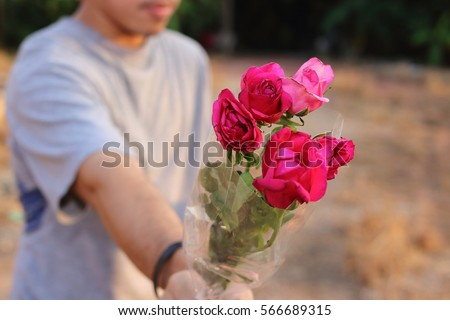 Selective focus and shallow depth of field of a beautiful bouquet of red roses are given with some person by young man. Love and romance Valentine's day concept.