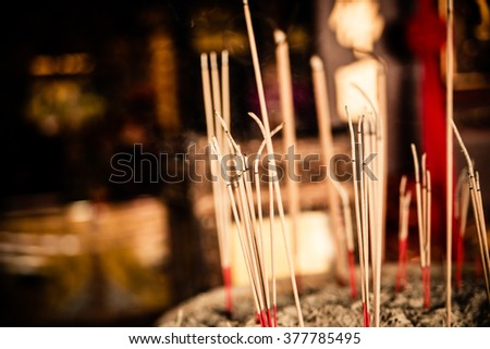 selective focus and vintage look of incense sticks in praying urn normally seen in chinese buddhist taoist temples as prayers offering to god and deities during chinese lunar new year - stock photo