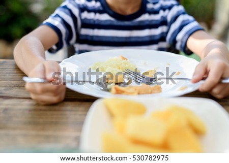 Selective focus at Young Thai boy eating with food on the wooden table with his family in the garden. And out focus tree background.