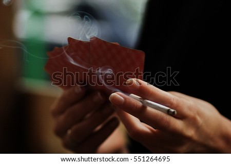 Selective focus blurry detail shot of a young woman's hands holding playing cards and a ladies' slim cigarette with a swirl of smoke