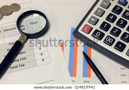 Selective focus calculator,magnifier,pen,coin on chart ,background.