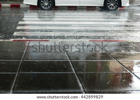 Selective focus , Car and Crosswalk and red white footpath in rainy season - stock photo