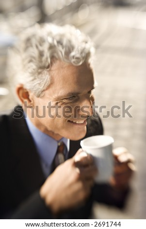 Selective focus close up of prime adult Caucasian man in suit drinking coffee and smiling.