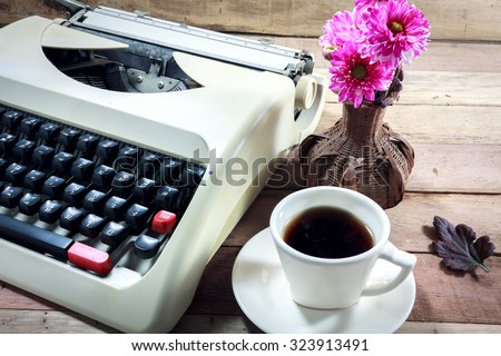 Selective focus cup of coffee,beautiful pink flower,old typewriter on wood background. - stock photo