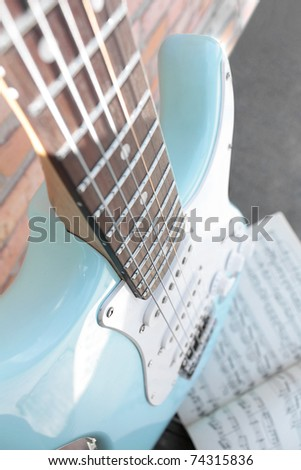 selective focus electric guitar with music sheet on a brick wall - stock photo