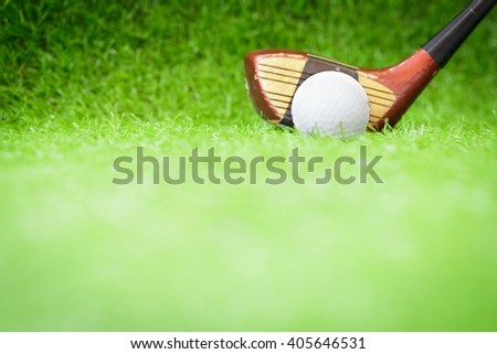 Selective focus golf ball and wood golf club on green grass background. - stock photo