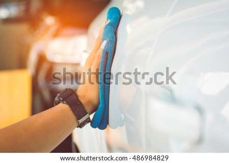 Selective focus hands man cleaning car with microfiber blue cloth,copy space.
