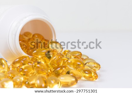 Selective focus image. Fish oil nutritional supplement capsules spilling out of a white pill bottle. - stock photo
