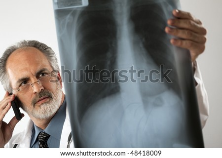Selective focus image of a doctor wearing glasses and a white lab coat and looking intently at an x-ray while using his cell phone. Horizontal shot. - stock photo