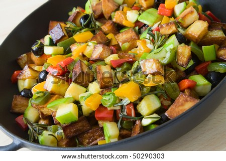 Selective focus image of a typical Greek pan-fried vegetables like pepper, olives, potatoes and zucchini.