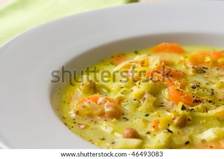 Selective focus image of a white plate with African peanut and garlic field soup.