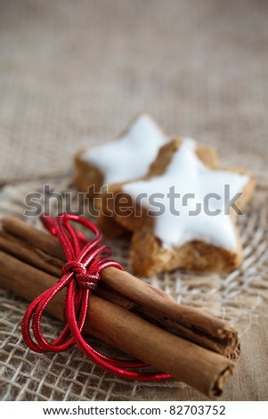 Selective focus image of cinnamon sticks and star-shaped cinnamon biscuits.