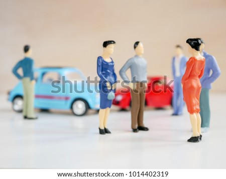 Selective focus image of miniature figures of people and car accident on white background / with copy space