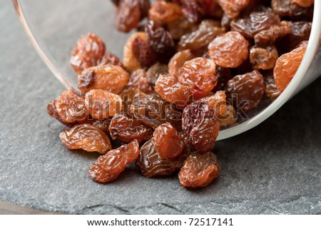 Selective focus image of raisins on a stone plate.