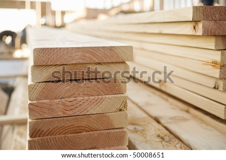 Selective focus image of stacks of lumber sitting at a construction site of a new home. Horizontal shot. - stock photo