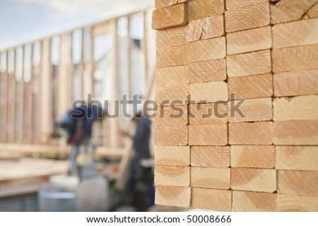 Selective focus image of stacks of 2x4 boards with construction workers and a building frame in the background. Horizontal shot. - stock photo