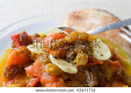 Selective focus image of tomato chutney in a glass bowl with a naan bread in the background - stock photo