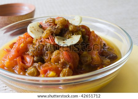 Selective focus image of tomato chutney in a glass bowl with beige colored background