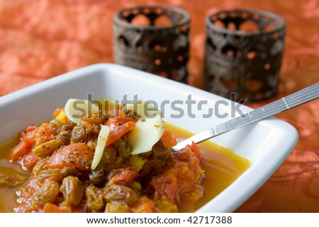 Selective focus image of tomato chutney in a white bowl with orange Indian fabric in background - stock photo