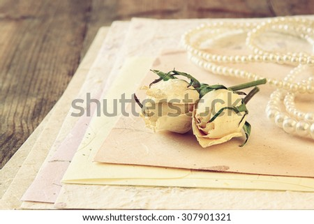 selective focus image of white dry roses, pearl necklace and hand made vintage letters paper on wooden table. retro filtered image