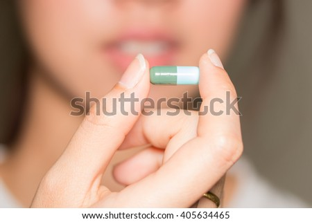 selective focus Medicine pills or capsules in hand, palm or fingers. Drug prescription for treatment medication. Woman, young female, person taking vitamin, painkiller, antibiotic - stock photo