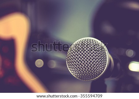 selective focus microphone and blur electric guitar background. - stock photo