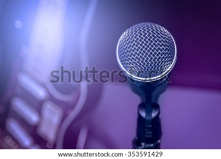 selective focus microphone and blur electric guitar background and flare light. - stock photo