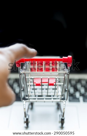 Selective focus : Mini red shopping cart on laptop with human hand for shopping online concept - stock photo