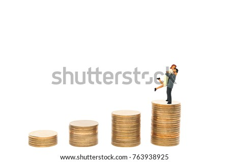 Selective focus miniature couple lover jumping hug success family life on top of golden coins stack, business growing up conception.