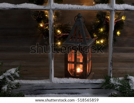 Selective focus of a glowing lantern and Christmas wreath through a snow covered window with fir branches.