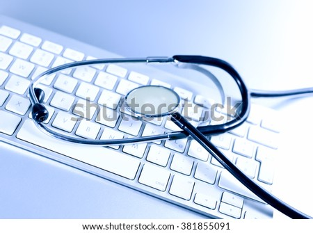 Selective focus of a stethoscope lying on a computer keyboard. Research or technical support theme. IT-Support.