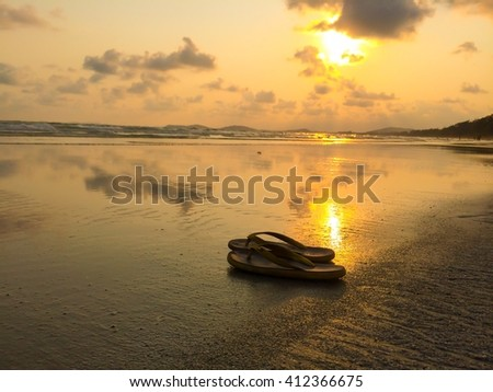 selective focus of Beach sandals or tongs on a sandy beach with lots of background copy space, silhouette tone  - stock photo