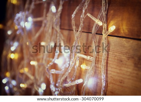 selective focus of Christmas warm gold garland lights on wooden rustic background. filtered image  - stock photo