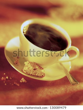 Selective focus of coffee cup with biscotti. - stock photo