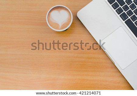 Selective focus of coffee latte art heart with blurred notebook (laptop) on workspace of wooden table. Concept for office workplace, freelance, coffee time, blogger, social, programmer, background - stock photo