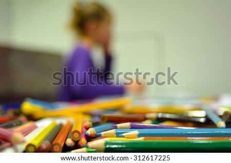 Selective focus of colour pencils in the foreground while a child, girl age 05,  thinking about art in the background. Horizontl (copy space) - stock photo
