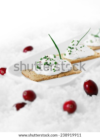 Selective focus of cream cheese canapes with chives against a white background on crushed ice. Copy space. - stock photo