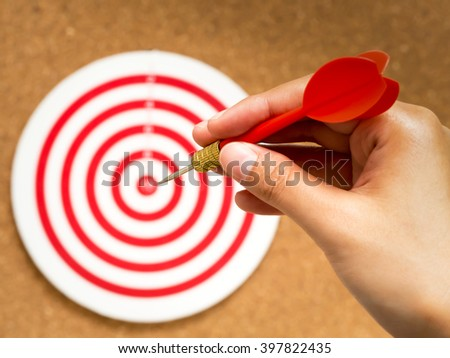 Selective focus of female hand holding red bullseye dart arrow point to target center of dartboard on cork background. Target and goal business concept. - stock photo